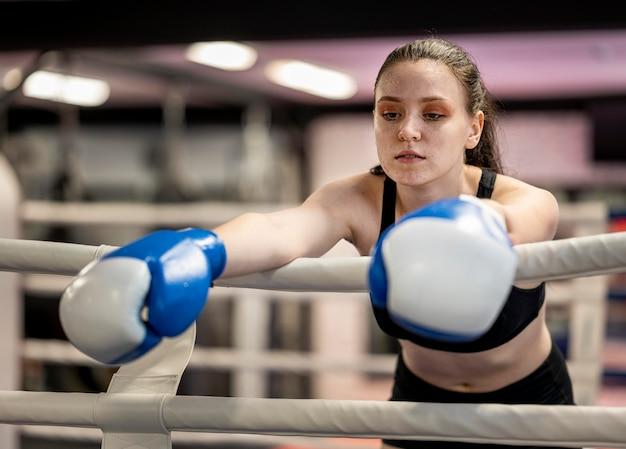 Vista frontal de la boxeadora con guantes protectores en el ring