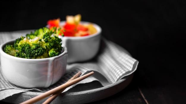 Vista frontal del brócoli en taza con palillos y tela