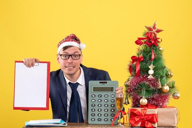 Vista frontal bsmiled hombre con gorro de papá noel sentado en la mesa cerca del árbol de navidad y presenta sobre fondo amarillo
