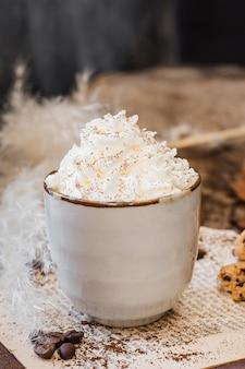 Vista frontal de café con leche y crema batida