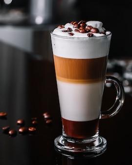 Vista frontal de café con leche con granos de café