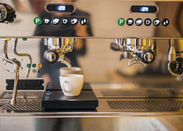 Vista frontal de la cafetera con taza