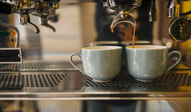 Vista frontal de la cafetera con tazas