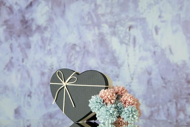 Vista frontal de la caja del corazón con flores de colores de tapa negra sobre fondo gris abstracto con espacio libre