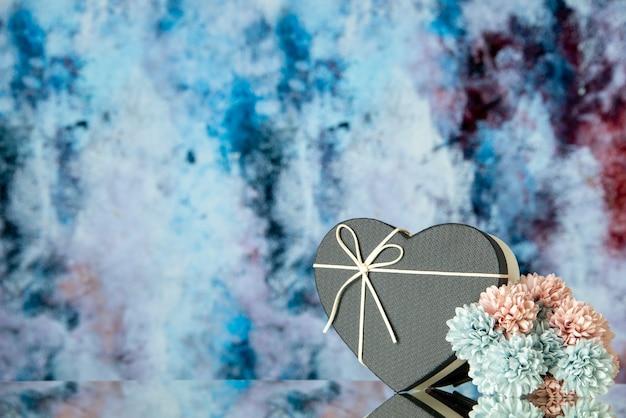 Vista frontal de la caja de corazón negro flores de colores sobre fondo abstracto