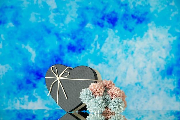Vista frontal de la caja en forma de corazón de flores de colores sobre fondo azul abstracto lugar de copia