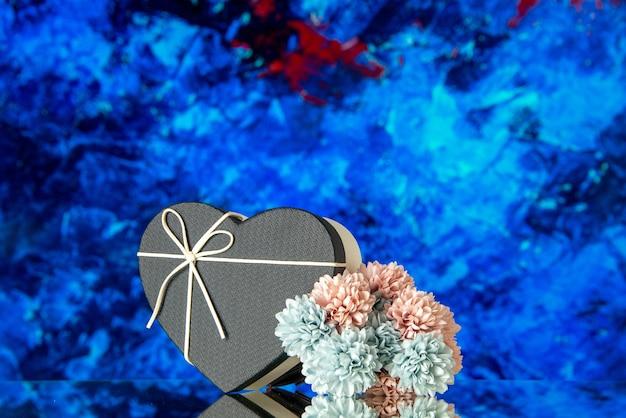 Vista frontal de la caja de regalo de corazón con tapa negra y flores de colores sobre fondo abstracto azul
