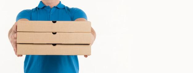 Vista frontal de cajas de pizza en manos del repartidor