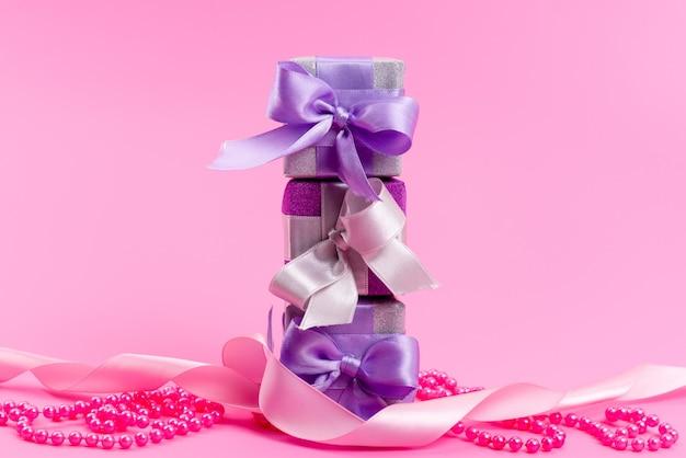 Una vista frontal de cajas de regalo de color púrpura con lazos en rosa
