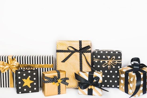 Vista frontal de cajas de regalo en varios colores negro, blanco y dorado.