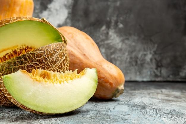 Vista frontal de calabaza fresca con melón sobre un fondo claro oscuro