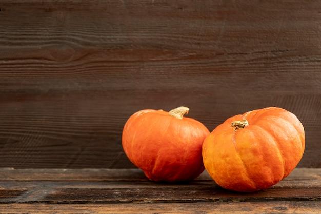 Vista frontal de calabazas naranjas en mesa de madera