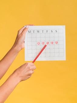 Vista frontal del calendario de menstruación con corazones y un lápiz