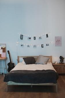 Vista frontal de una cama con cuerda de fotos en la parte superior