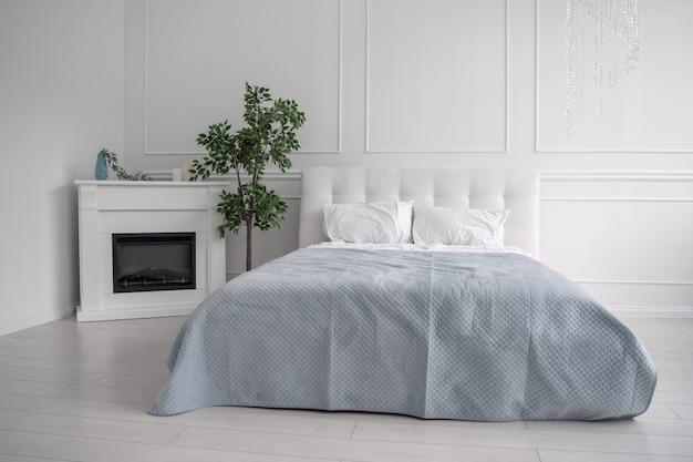 Vista frontal de la cama de cuero blanco y sábana azul en habitación blanca brillante