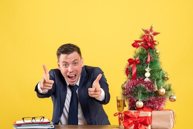 Vista frontal de la cámara señalando con el dedo hombre eufórico sentado en la mesa cerca del árbol de navidad y presenta en amarillo