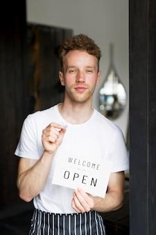 Vista frontal del camarero masculino con cartel de bienvenida