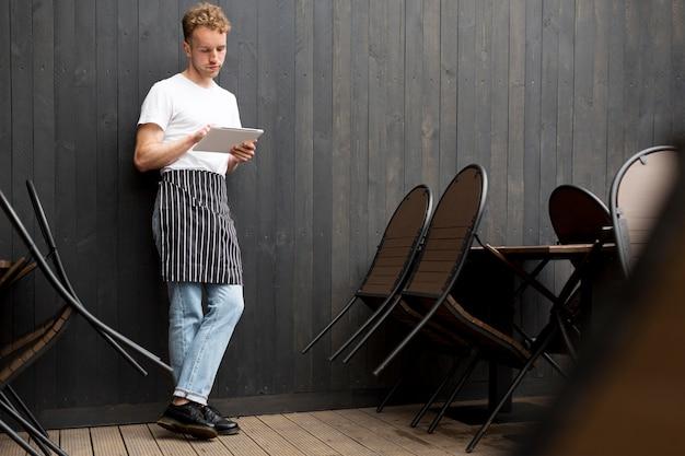 Vista frontal del camarero masculino con delantal y tableta