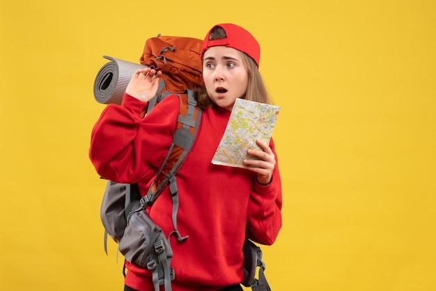 Vista frontal del caminante de niña confundida con mochila roja con mapa