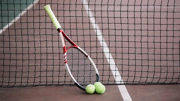 Vista frontal del campo de juego de tenis con raqueta