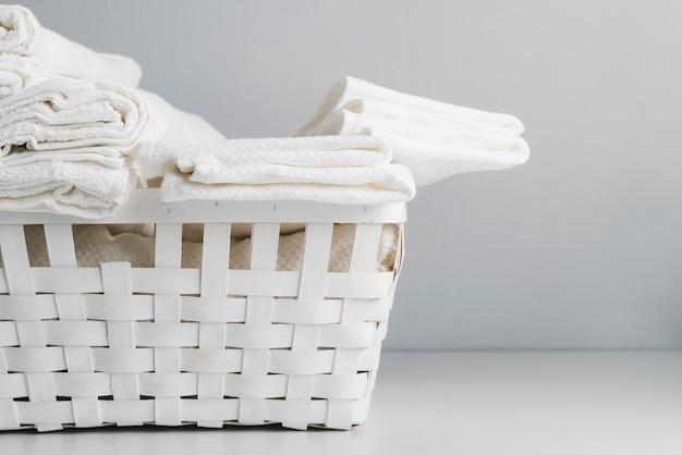 Vista frontal canasta blanca con toallas