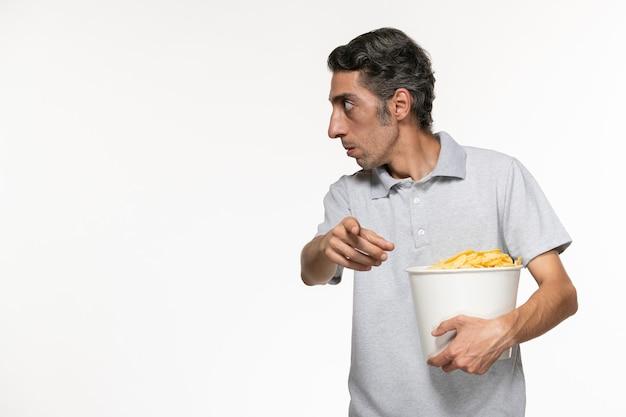 Vista frontal de la canasta de explotación masculina joven con papas fritas hablando con alguien sobre la superficie blanca