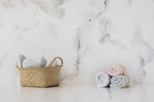 Vista frontal de la canasta y toallas en la mesa con fondo de mármol y espacio de copia