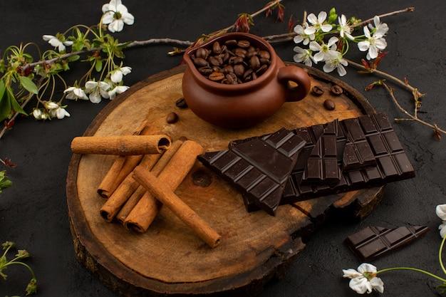 Vista frontal canela fresca junto con chocolate amargo en el escritorio de madera alrededor de flores blancas en el piso oscuro