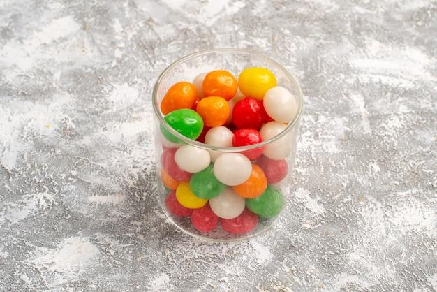 Vista frontal de caramelos de colores dentro de un vaso pequeño en el espacio en blanco