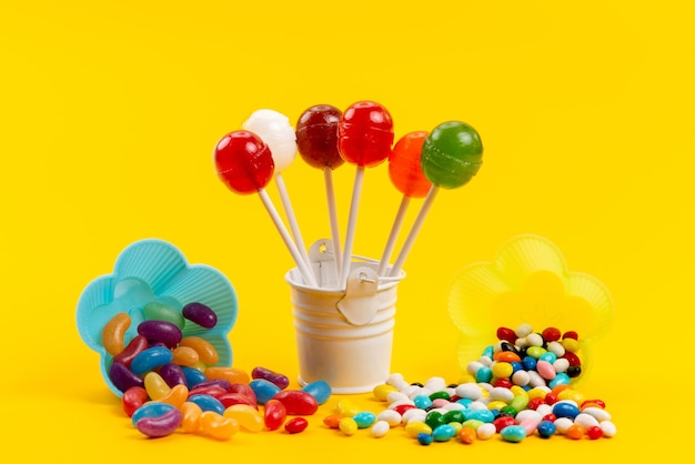 Una vista frontal de caramelos de colores junto con piruletas aisladas en amarillo, dulce color azúcar