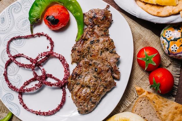 Vista frontal carne basturma kebab con tomate y pimiento picante a la parrilla con cebolla en zumaque