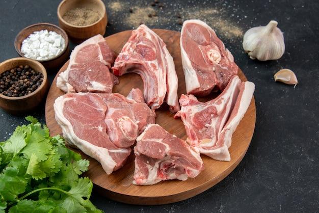 Vista frontal de la carne fresca rebanadas de carne cruda con condimentos sobre fondo gris comida comida frescura comida de vaca animal de cocina