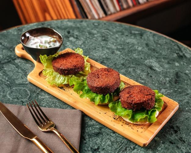 Una vista frontal de carne frita picada junto con ensalada verde en el escritorio de madera marrón y pared de luz