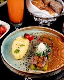 Vista frontal de carne frita sobre espárragos con puré de papas y hierbas en un plato
