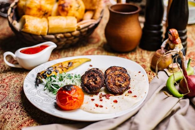 Vista frontal de carne a la parrilla sobre pan de pita con tomate y cebolla