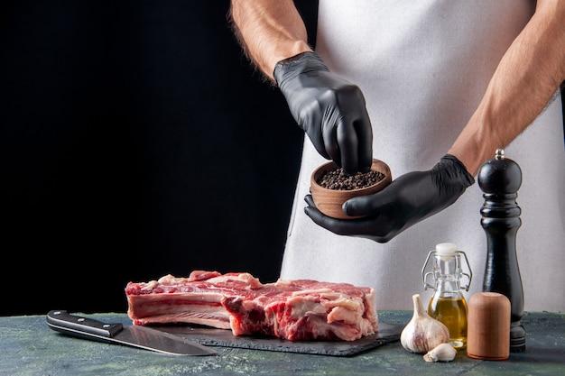Vista frontal de carnicero macho vertiendo pimienta en una rebanada de carne sobre una superficie oscura