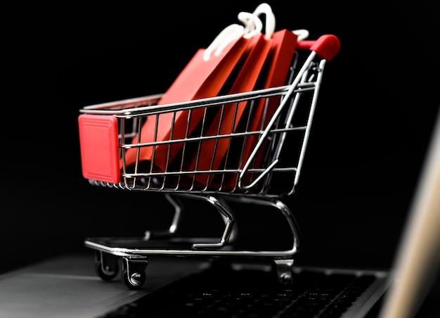 Vista frontal del carrito de compras de cyber monday con bolsas