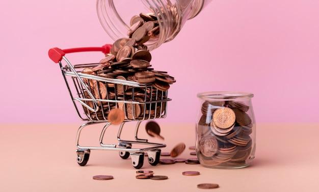 Vista frontal del carrito de compras con muchas monedas y jarra