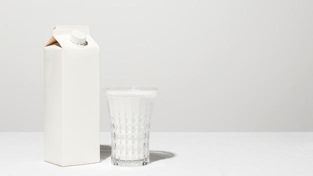 Vista frontal del cartón de leche con vaso lleno y espacio de copia