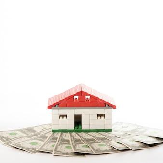 Vista frontal de la casa con billetes de dinero