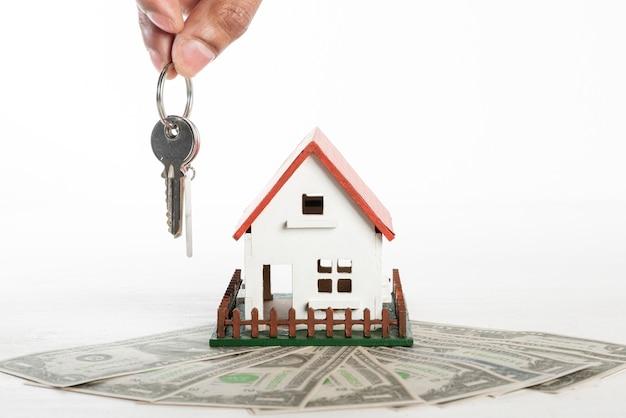 Vista frontal de la casa y el dinero con la persona que tiene las llaves