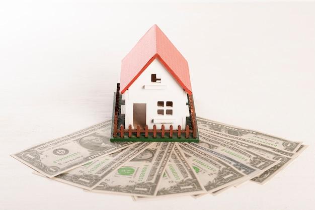 Vista frontal de la casa con jardín y billetes de dinero