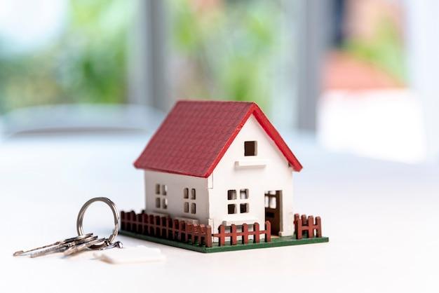 Vista frontal de la casa modelo de juguete y llaves en el fondo borroso