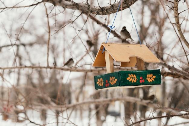 Vista frontal de la casita para aves colgando del árbol exterior en invierno