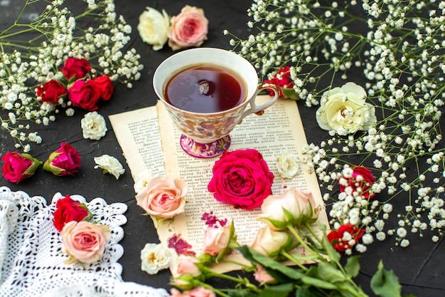 Una vista frontal de cerca té caliente en el papel y alrededor de rosas de diferentes colores en la superficie gris