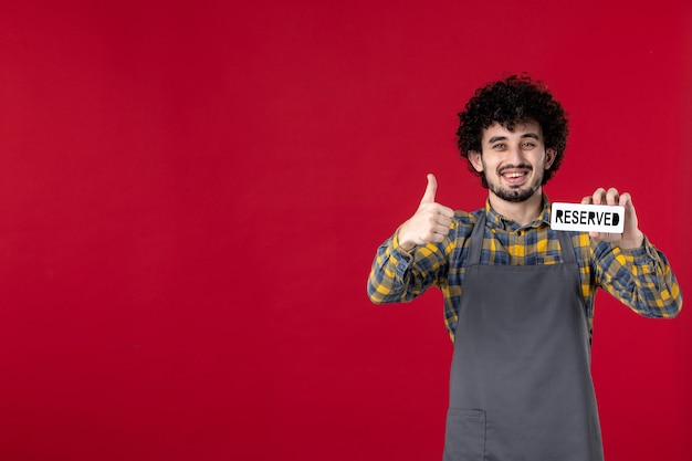 Vista frontal cercana del camarero sonriente del hombre con el pelo rizado sosteniendo el icono reservado y haciendo el gesto de ok sobre fondo rojo aislado