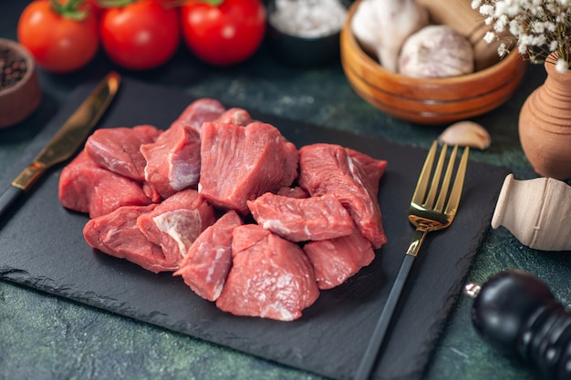 Vista frontal cercana de carnes frescas picadas crudas y cubiertos en tablero de madera
