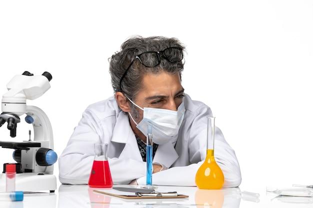 Vista frontal cercana científico de mediana edad en traje especial sentado con soluciones sobre fondo blanco ciencia de virus masculino covid química
