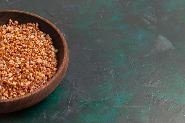 Vista frontal cercana comida sabrosa de trigo sarraceno cocido dentro de la placa marrón sobre la superficie verde oscuro