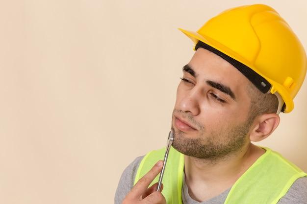 Vista frontal cercana constructor masculino en casco amarillo posando con herramienta plateada en escritorio ligero